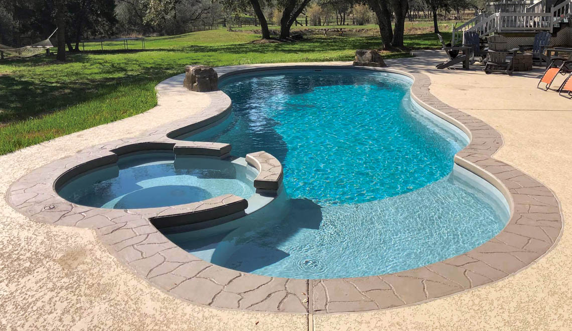 Leisure Pools Allure large fiberglass swimming pool with built-in spa and splash deck