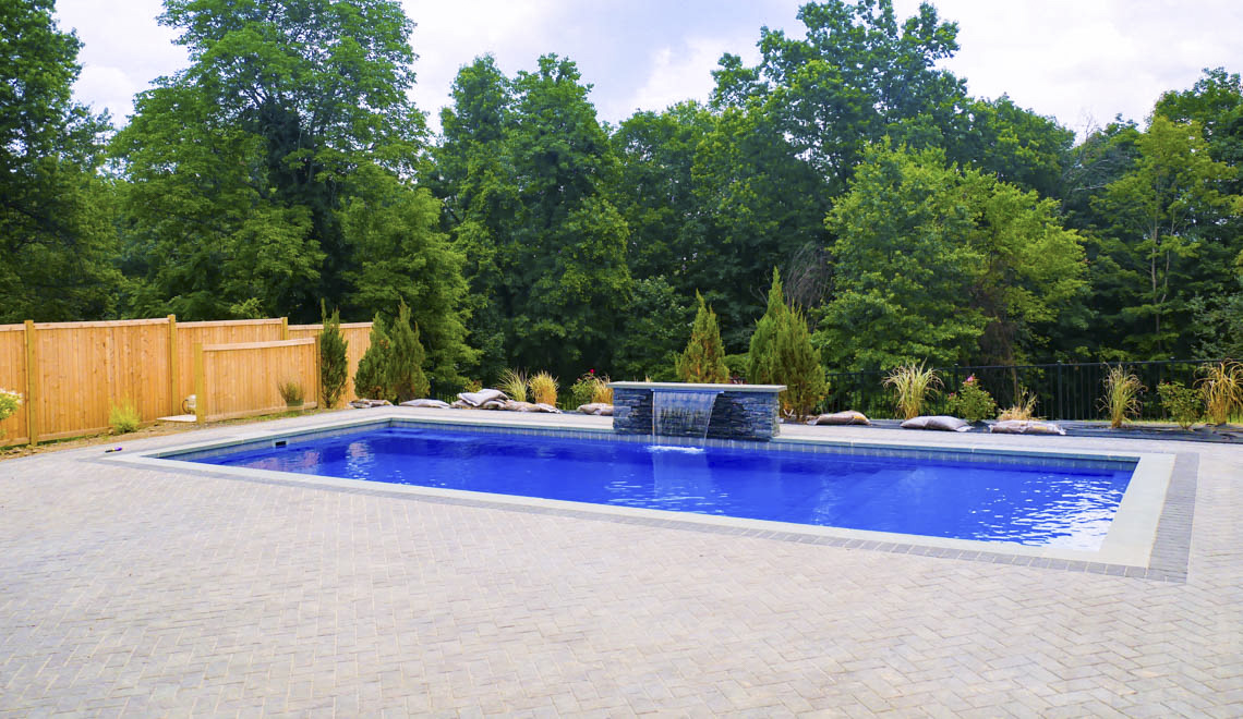Leisure Pools Pinnacle large fiberglass swimming pool with built-in splash deck