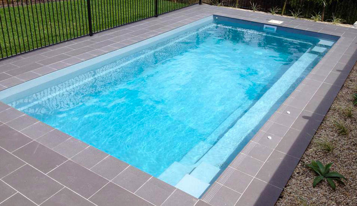 Leisure Pools Reflection composite fiberglass swimming pool with full-length bench seat