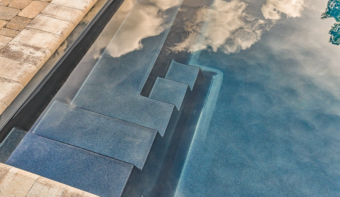 Leisure Pools Infinity composite swimming pool with built-in steps and bench