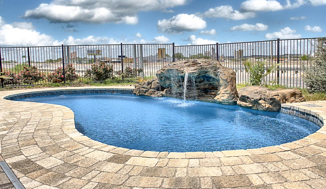 Leisure Pools Tuscany freeform fiberglass swimming pool with perimeter safety ledge