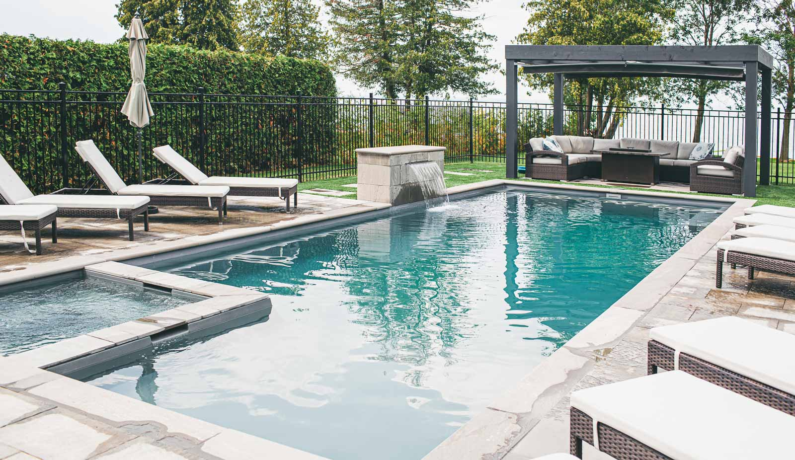 Leisure Pools Ultimate fiberglass swimming pool with built-in spa and tanning ledge