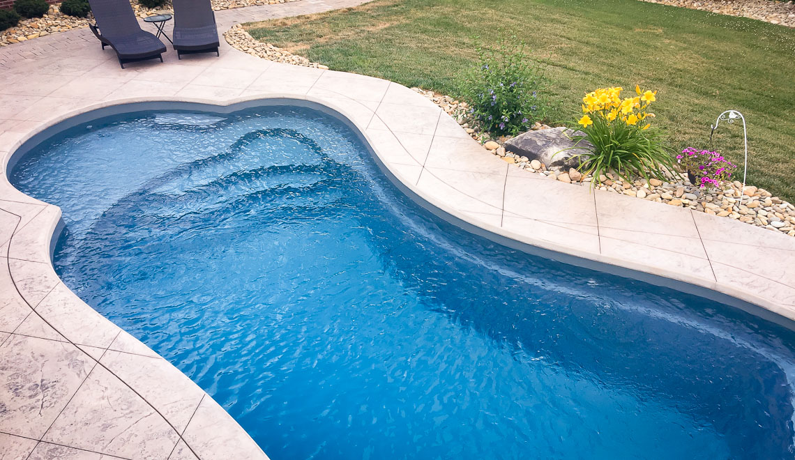 Leisure Pools Eclipse freeform in-ground swimming pool with built-in splash deck