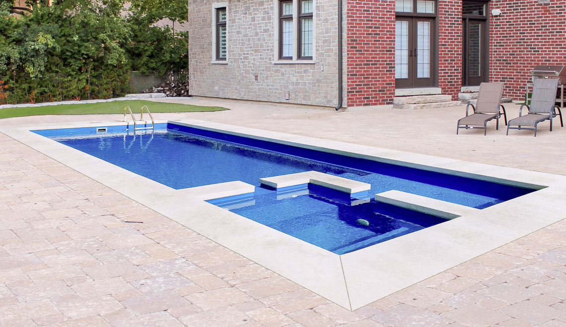 Leisure Pools Limitless composite fiberglass swimming pool with built-in spa, splash deck and bench