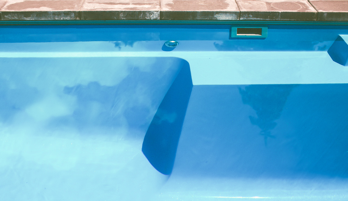 Leisure Pools Limitless precast fiberglass swimming pool with built-in spa, splash deck and bench